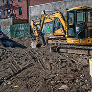 Link-Belt excavator trenching for lifting and moving material rock and soil site for new building.<br />