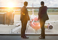 Mature businessmen standing while looking on the plane in airport