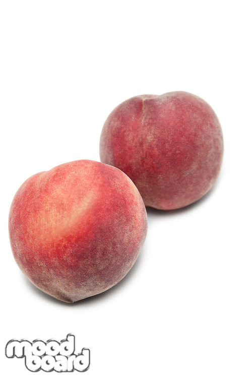 Two peaches against white background