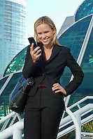 Businesswoman text messaging outside office building