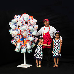Portrait of concession worker Milciades Jiminez with his daughters Allison and Alina.<br />