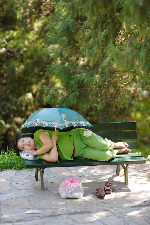A lady asleep in a garden bench holding an umbrella.