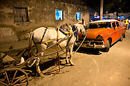 Horse and old car at night in Santiago de Cuba, Cuba.