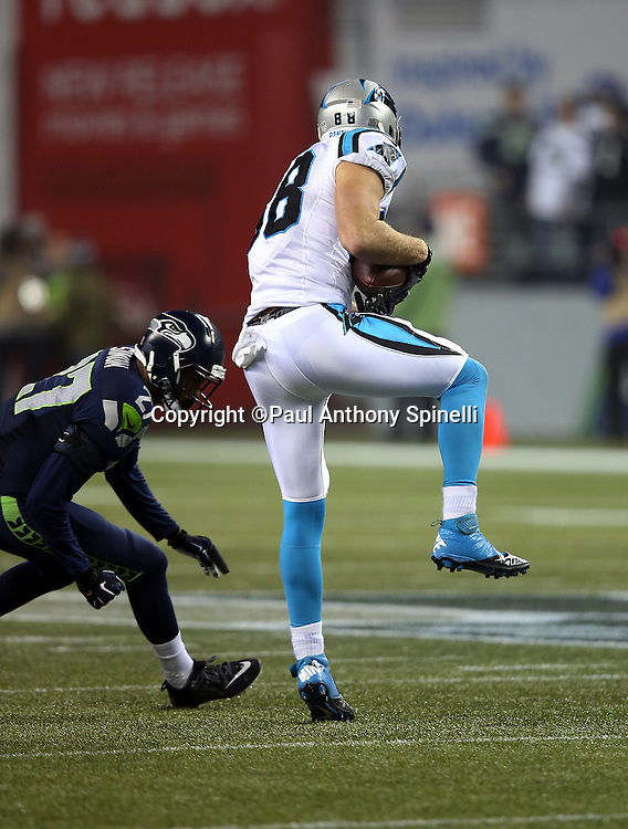 Carolina Panthers tight end Greg Olsen (88) gets tackled by Seattle Seahawks cornerback Tharold Simon (27) as he catches a third quarter pass for a first down during the NFL week 19 NFC Divisional Playoff football game against the Seattle Seahawks on Saturday, Jan. 10, 2015 in Seattle. The Seahawks won the game 31-17. ©Paul Anthony Spinelli