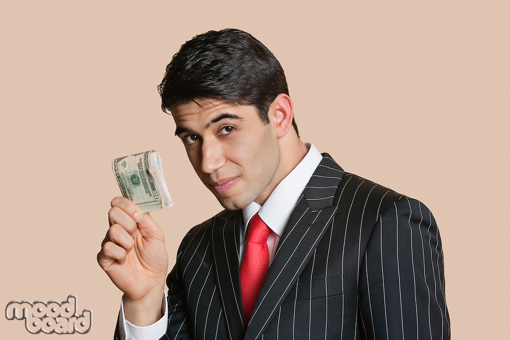Portrait of a young businessman showing paper money over colored background