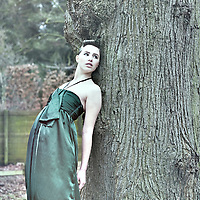 Young woman wearing a green party dress standing alone outdoors leaning against a large tree