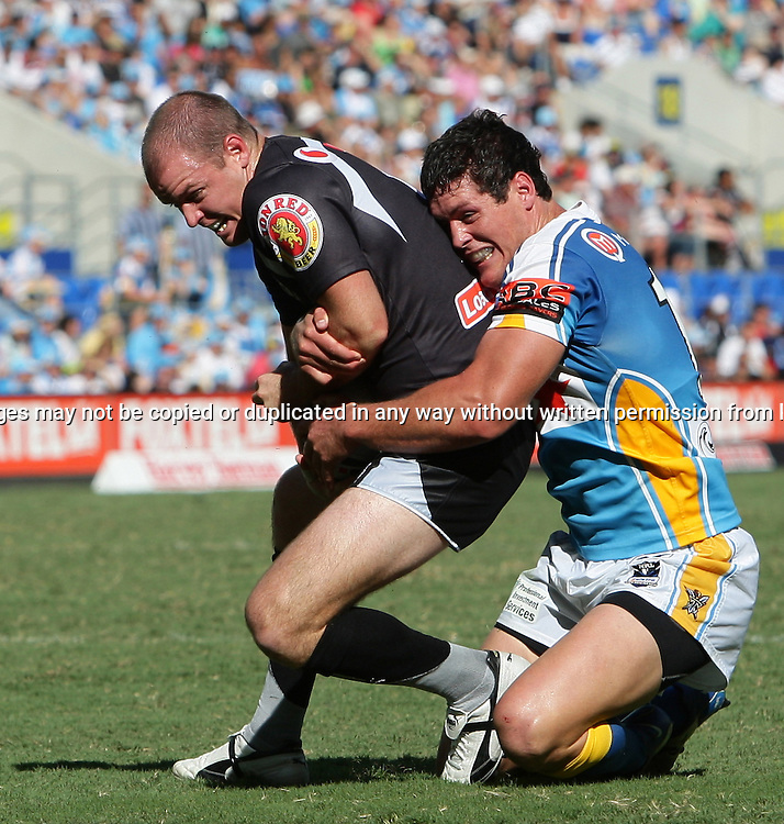 Nathan Fien is pulled down by Josh Graham just short of the try line during round 7 of the NRL - Gold Coast Titans v New Zealand Warriors. Played at Skilled Stadium, Robina QLD. Titans (36) defeated the Warriors (24).  Photo: Warren Keir (Photosport NZ).<br /> <br /> Use information: This image is intended for Editorial use only (e.g. news or commentary, print or electronic). Any commercial or promotional use requires additional clearance.