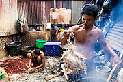 17 JUNE 2013 - YANGON, MYANMAR:  Chickens are killed and plucked near Aung Mingalar Jetty in Yangon. Yangon, formerly Rangoon, is the largest city in Myanmar. It is the former capital of the Southeast Asian country. It's still Myanmar's economic capital.   PHOTO BY JACK KURTZ
