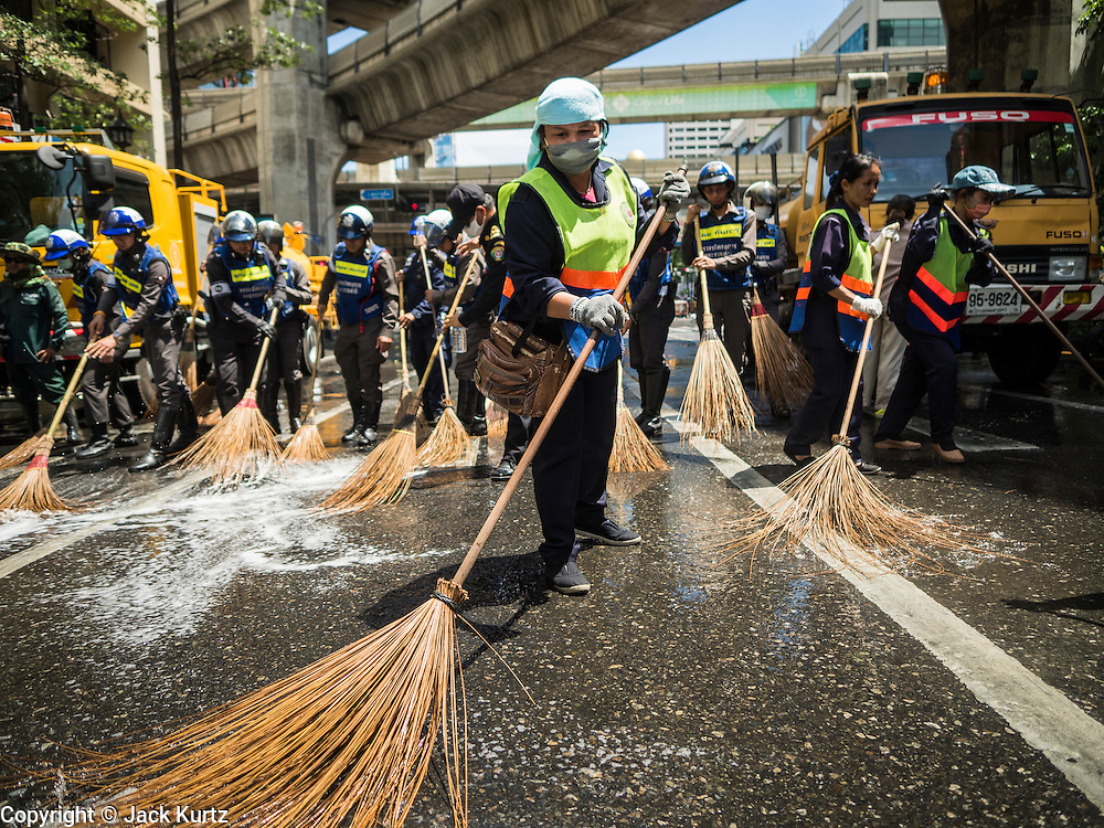 18 AUGUST 2015 - BANGKOK, THAILAND: Bangkok street cleans wash the street in front of Erawan Shrine Tuesday. The street was covered in debris after a bomb went off in the shrine. An explosion at Erawan Shrine, a popular tourist attraction and important religious shrine in the heart of the Bangkok shopping district, killed at least 20 people and injured more than 120 others, including foreign tourists, during the Monday evening rush hour. Twelve of the dead were killed at the scene. Thai police said an Improvised Explosive Device (IED) was detonated at 18.55. Police said the bomb was made of more than six pounds of explosives stuffed in a pipe and wrapped with white cloth. Its destructive radius was estimated at 100 meters.    PHOTO BY JACK KURTZ