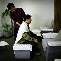 BEIJING, APRIL-22, 2010:  a customer gets a massage while waiting for his car at the BMW dealership .