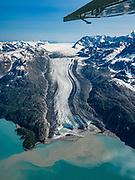 """This massive landslide across Lamplugh Glacier crashed from a 4000-foot-high mountainside collapsing in Glacier Bay National Park on June 28, 2016. The debris will eventually be carried 10 miles into Johns Hopkins Inlet. The Fairweather Range comprises the southernmost of the Saint Elias Mountains. Flightseeing from Skagway or Haines is a spectacular way to see Glacier Bay National Park, in Alaska, USA. We were bedazzled by Mountain Flying Service's 1.3-hour West Arm tour from Skagway. Glacier Bay is honored by UNESCO as part of a huge Biosphere Reserve and World Heritage site shared between Canada and the United States. In 1750-80, Glacier Bay was totally covered by ice, which has since radically melted away. In 1794, Captain George Vancover found Icy Strait on the Gulf of Alaska choked with ice, and all but a 3-mile indentation of Glacier Bay was filled by a huge tongue of the Grand Pacific Glacier, 4000 feet deep and 20 miles wide. By 1879, naturalist John Muir reported that the ice had retreated 48 miles up the bay. In 1890, """"Glacier Bay"""" was named by Captain Beardslee of the U.S. Navy. Over the last 200 years, melting glaciers have exposed 65 miles of ocean. As of 2019, glaciers cover only 27% of the Park area. Since the mid 1900s, Alaska has warmed 3 degrees Fahrenheit and its winters have warmed nearly 6 degrees. Human-caused climate change induced by emissions of greenhouse gases continues to accelerate warming at an unprecedented rate. Climate change is having disproportionate effects in the Arctic, which is heating up twice as fast as the rest of Earth."""