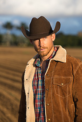 hot cowboy outdoors at sunset on a ranch