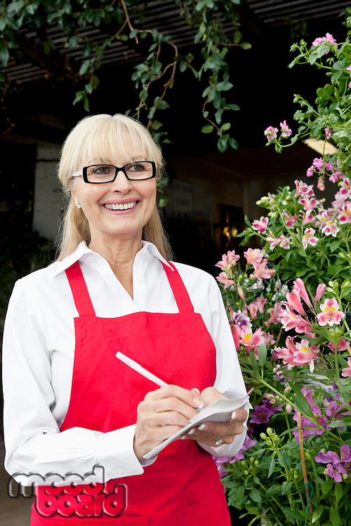 Happy senior florist making notes while looking away
