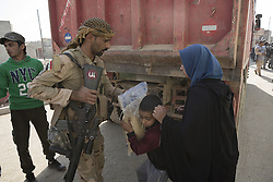 November 11, 2016 - Mosul, Nineveh, Iraq - 11/11/2016. Mosul, Iraq. A soldier, of the Iraqi Army's 9th Armoured Division, hands a sack of food to a female resident of Mosul's Al Intisar district during a visit by his unit. The Al Intisar district was taken four days ago by Iraqi Security Forces (ISF) and, despite its proximity to ongoing fighting between ISF and ISIS militants, many residents still live in the settlement without regular power and water and with dwindling food supplies...The battle to retake Mosul, which fell June 2014, started on the 16th of October 2016 with Iraqi Security Forces eventually reaching the city on the 1st of November. Since then elements of the Iraq Army and Police have succeeded in pushing into the city and retaking several neighbourhoods allowing civilians living there to be evacuated - though many more remain trapped within Mosul. (Credit Image: © Matt Cetti-Roberts via ZUMA Wire)
