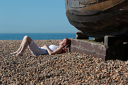 © Licensed to London News Pictures. 08/06/2014. Brighton, UK. A woman sunbathing on Brighton beach. with temperatures expected to be high Brighton is looking forward to another bumper Sunday for businesses.  Photo credit : Hugo Michiels/LNP