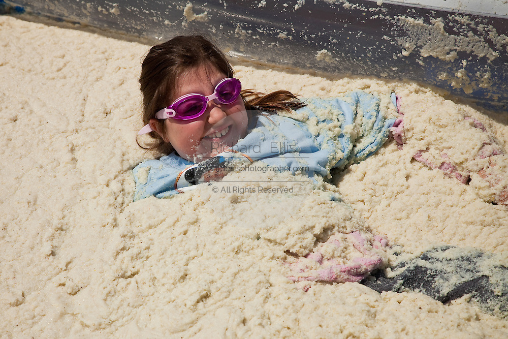 ST GEORGE, SC - APRIL 17: A young girl rolls around in a giant vat of grits during the World Grits Festival April 17, 2010 in St. George, South Carolina. Among the various events for the festival is the Rolling in the Grits for children where the winner is the one who can hold the most of grits to their body. Grits is corn-based porridge common in the Southern United States.   (Photo Richard Ellis)