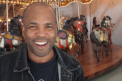 Man smiling in front of a merry go round