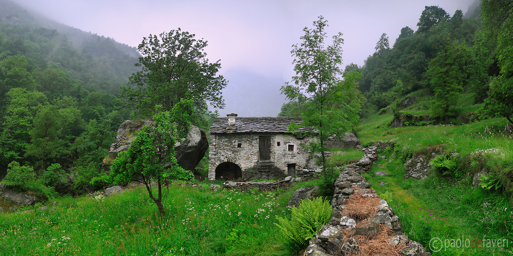 An old  house of wood and stones lies in a small field dotted with wildflowers. Taken an overcast day in Valchiusella, a small valley in the Western Alps in Piedmont, Italy, an enchanted place where time seems to have stopped. This is stitched from six vertical frames.