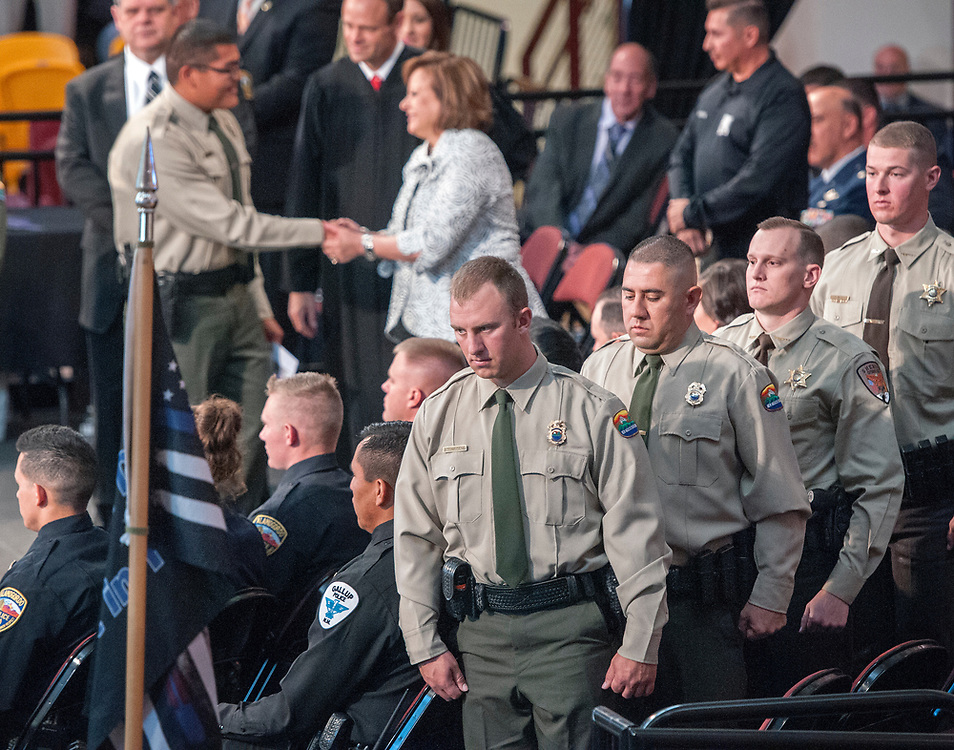 em051817f/jnorth/Cadet Jacob Townsend, center, with the NM State Parks, and others wait to received their diplomas during the graduation ceremony for the Basic Police Officer Training Class 194. Fifty-eighty cadets were sworn in as officers for law enforcement agencies around the state during the ceremony held at Santa Fe Indian School, in Santa Fe, Thursday May 18, 2017. Behind them Gov. Susana Martinez congratulates cadets. (Eddie Moore/Albuquerque Journal