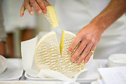 """A slice of soft cheese is cut and removed for tasting during the British Cheese Awards at the Royal Bath & West show in Somerset, where more than 1,000 British cheeses are vying for the title of supreme champion at an event designed to a be a """"great celebration"""" of the industry."""