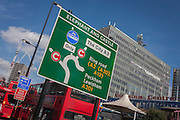 London buses and a traffic sign showing the new road layout with the soon to be demolished Shopping Centre (right) at Elephant & Castle, south London.