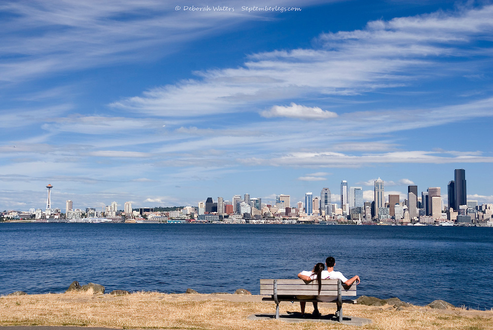 Couple sitting on a bench enjoying the view across Elliott Bay to downtown Seattle and the Space Needle, view from Alki, West Seattle, USA
