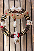 A low country style Christmas wreath made from cotton balls and vine hangs from the Slavery Museum along Chalmers Street in Charleston, SC.