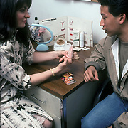Birth Control Counseling - NYU college campus clinic - male student shown how to use condom the correct way