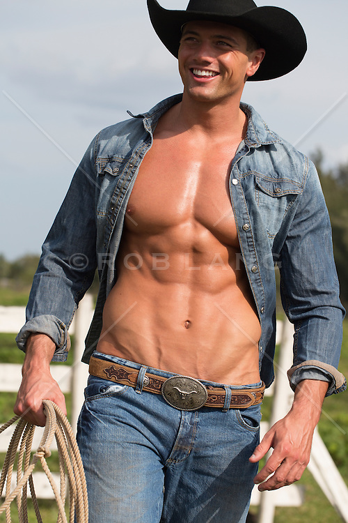 muscular cowboy with an open shirt smiling and walking outdoors on a ranch