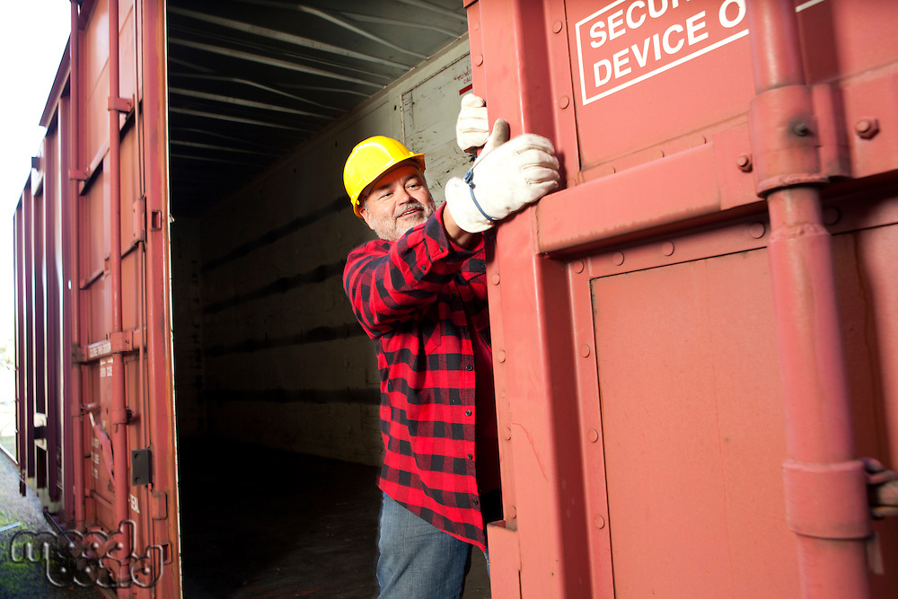 Middle Aged worker closing industrial railway carriage