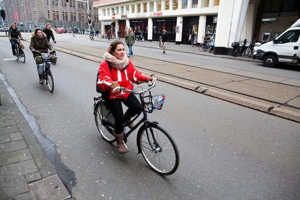 In Amsterdam rijden toeristen op een huurfiets door de Vijzelstraat.<br /> <br /> In Amsterdam tourist ride a rental bike at the Vijzelstraat.