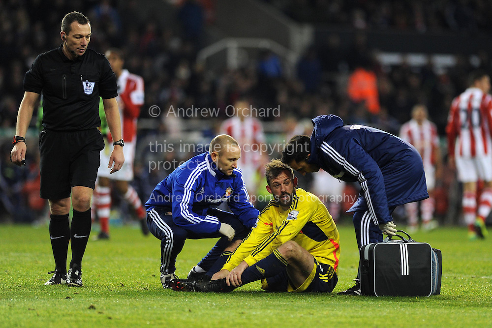 Steven Fletcher of Sunderland receives treatment after collision with Stoke keeper Asmir Begovic as the ref Kevin Friend looks on. Barclays Premier league, Stoke city v Sunderland at the Britannia stadium in Stoke on Trent, England on Saturday 23rd Nov 2013. pic by Andrew Orchard, Andrew Orchard sports photography,