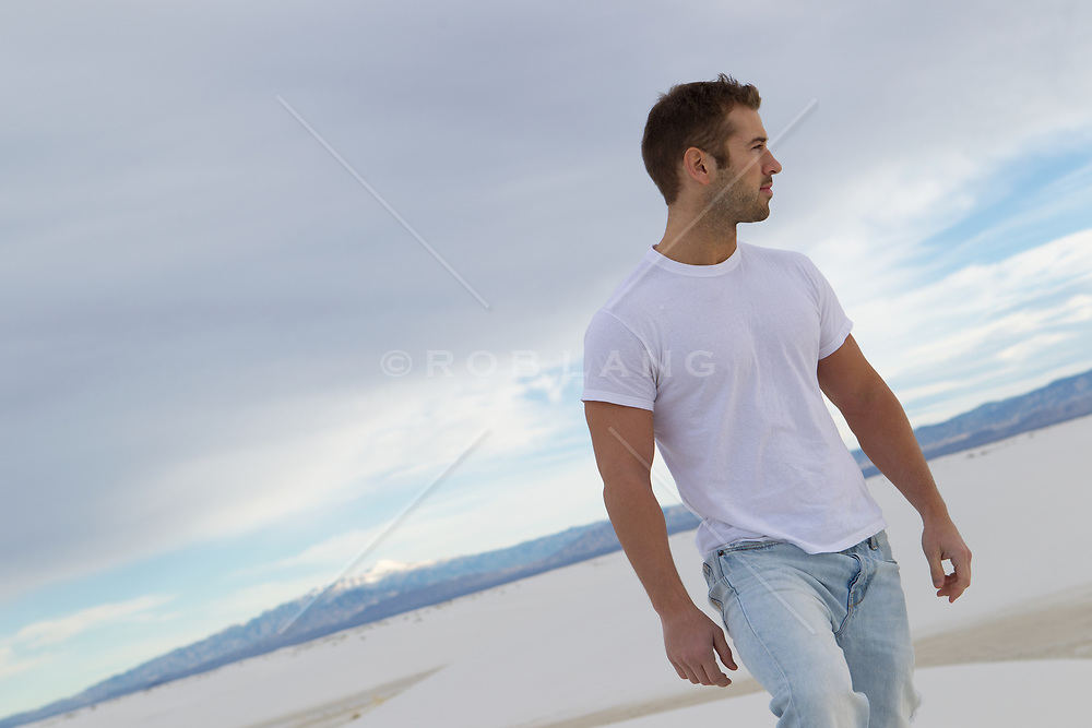 handsome man in a tee shirt and jeans out in the desert