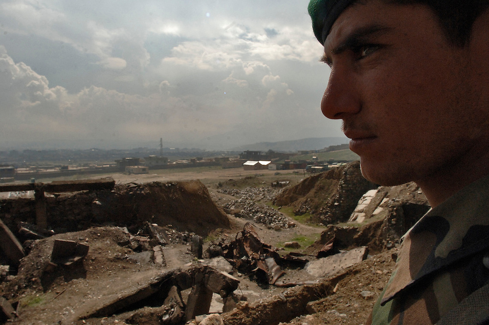 Infantry Soldier Jamal Naser stands guard over underground fuel facilities. The large crater in front of him is the result of what Afghanistan National Army personnel say was a bomb from a B-52 Stratofortress bomber. The small pipeline, running out of the crater, is one of the functioning fuel lines that provides a gravity feed to a fuel truck fillstand.  U.S Air Force  specialists are manning Embedded Training Teams that fulfill an U.S. Army request for forces in support of an Office of Security Cooperation-Afghanistan (OSC-A) mission to advise, train and mentor Afghanistan National Army personnel on the U.S. Army logistics standard and methods.  The mentoring will allow the ANA to operate safely and prepare for future missions. OSC-A in its partnership with the Government of Afghanistan and the International Community plan, program, and implement reform in Defense Sectors, develop a stable Afghanistan, and deter and defeat terrorism within its borders. (U.S. Air Force photo/Master Sgt. Lance Cheung)..<br />