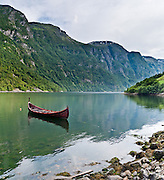 Norwegian boat. Fjordland mountain cliffs rise above Nærøyfjord, a UNESCO World Heritage Site in Norway. Panorama stitched from 3 overlapping photos.