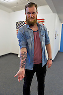Garden City, New York, USA. September 13, 2015. JAKOB RAGNVALDSSON, from Iceland, displays his tattoo created by his cousin Gunnar Valdimarsson, at the United Ink Flight 915 Tattoo convention at the Cradle of Aviation Museum in Long Island. The realistic tattooon his arm depicts his grandfather and himself as a boy.