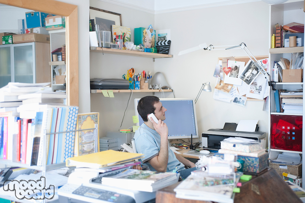 Creative professional sits on phone in corner of office
