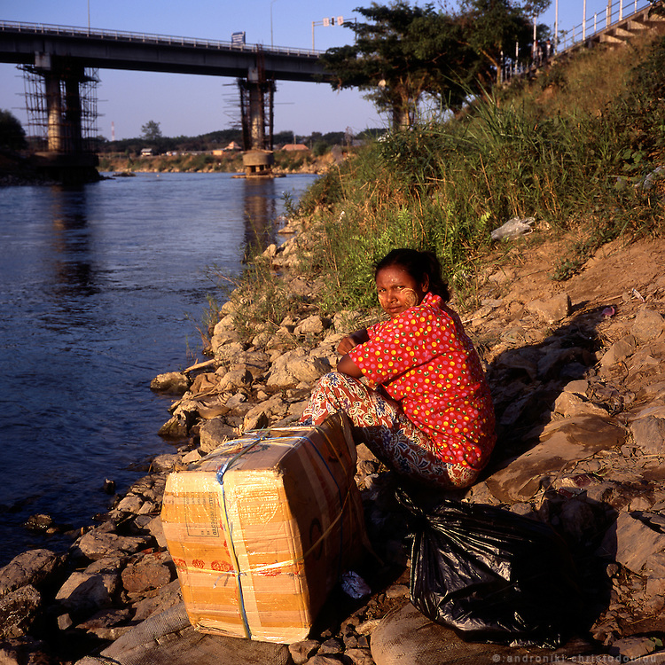 Woman waiting to cross the river via the illegal crossing of people and goods between Burma and Thailand on a inflated track-tire tube that is pushed back and forth through the river on a regular basis, a few hundrends of meters away from the bridge that is the official border crossing.