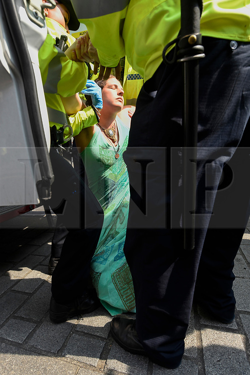 "© Licensed to London News Pictures. 17/04/2019. LONDON, UK.  Police officers arrest a protester at Oxford Circus during ""London: International Rebellion"", on day three of a protest organised by Extinction Rebellion, demanding that governments take action against climate change.  Marble Arch, Oxford Circus, Piccadilly Circus, Waterloo Bridge and Parliament Square have been blocked by activists in the last three days.  Police have issued a section 14 order requiring protesters to convene at Marble Arch only so that the protest can continue.  Photo credit: Stephen Chung/LNP"