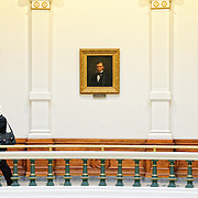 A man talks on his cell phone one one of the balconies overlooking the main atrium in the Texas State Capitol Building in Austin, Texas. Behind him are three painted portraits on the wall.