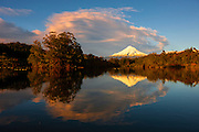 Taranaki, also known as Mount Egmont, is reflected in the waters of Lake Mangamahoe near New Plymouth, New Zealand at sunrise. Red and pink clouds, colored by the warm light of sunrise, arc over the mountain and lake. The 8,261-foot (2,518-meter) mountain is still considered an active volcano; it last erupted in 1854.