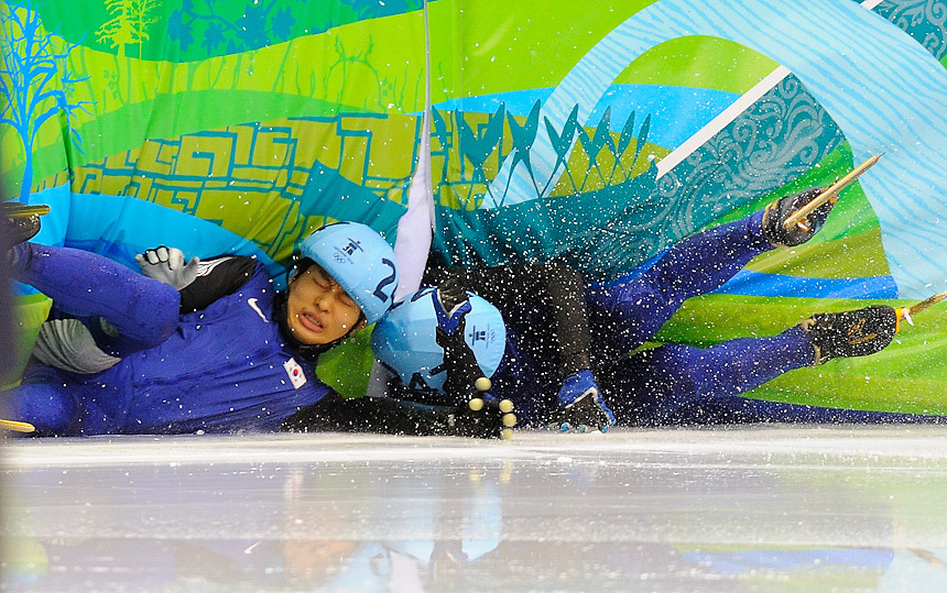 Korea's Sung Si-Bak (L) and Korea's Lee Ho-Suk crash into the pads just meters from the finish line during the men's 1500 meter finals in short track speed skating at Pacific Coliseum on day 2 of the Vancouver 2010 winter olympics.