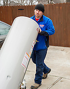 Joe Rosenblum, with Allied Plumbing, carries an old water heater to his truck on Wednesday, March 19, 2014, in Rogers, Ark. Rosenblum was replacing the water heaters in a home in Rogers, Ark. Photo by Beth Hall
