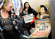 "Claudette Bleidner, center, of Southbury, Conn., stands next to a caricature  she made of Gov. Dannel P. Malloy dressed as a Redcoat soldier, as a woman reads information of upcoming gun legislation during a ""lobby day"" held by the National Rifle Association and and other gun rights groups at the Legislative Office Building in Hartford, Conn., Monday, March 11, 2013. Both sides of the gun control issue are increasing pressure on Connecticut lawmakers, who are close to voting on changes to state law stemming from the deadly shooting at Sandy Hook Elementary School in Newtown. (AP Photo/Jessica Hill)"