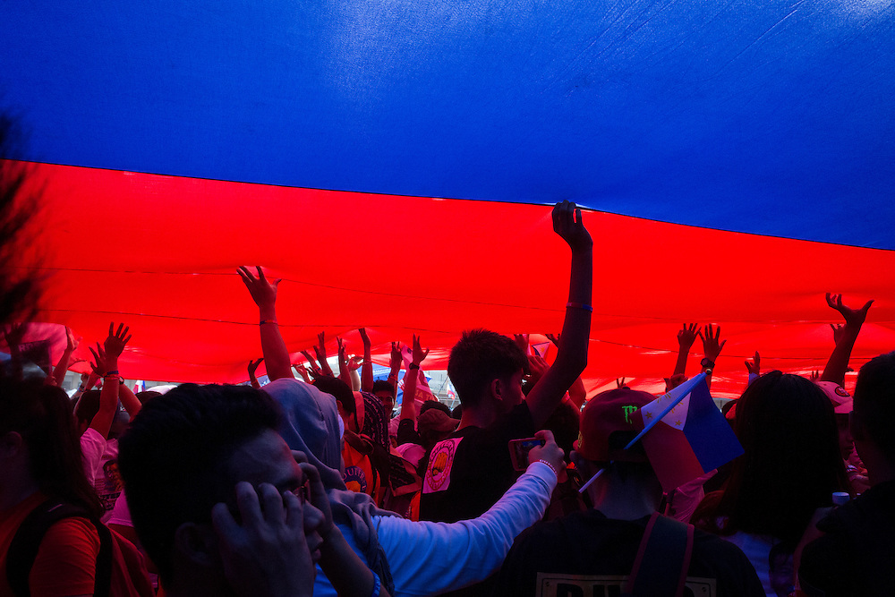 MANILA, PHILIPPINES - MAY 7: Supporters of Mayor Rodrigo &quot;Digong&quot; Duterte under a huge Philippine flag that was parading in the grounds of Luneta Park just before the speech of candidates in meeting de advance in Luneta Grand Stand, Manila, Philippines on Saturday, May 7, 2016. Rodrigo &quot;Digong&quot; Duterte runs for president in the 2016 Philippine national election that  will be held on May 9, 2016.<br /> <br /> Photo by Richard A. de Guzman