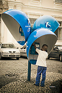 A elementary age Brazilian child making a phone call at a public phone booth in Salvador, Brazil.
