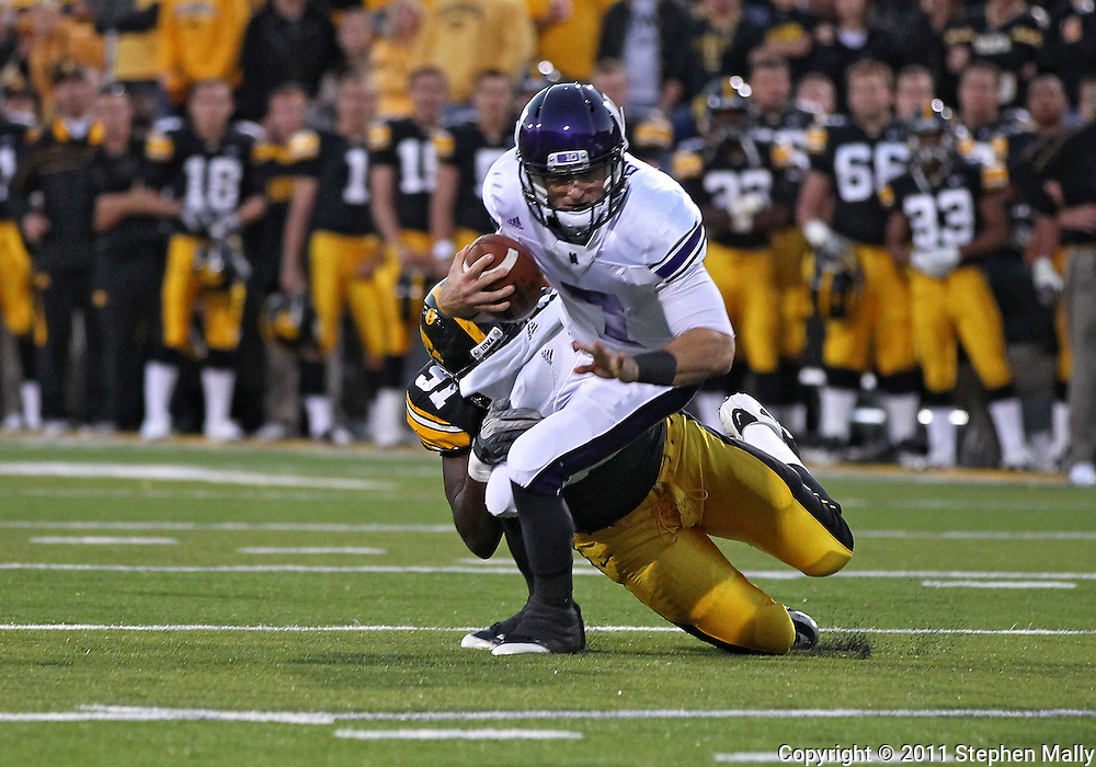 October 15, 2011: Iowa Hawkeyes defensive lineman Broderick Binns (91) tries to pull down Northwestern Wildcats quarterback Dan Persa (7) during the first half of the NCAA football game between the Northwestern Wildcats and the Iowa Hawkeyes at Kinnick Stadium in Iowa City, Iowa on Saturday, October 15, 2011. Iowa defeated Northwestern 41-31.