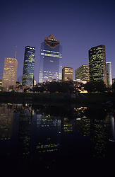 Houston, Texas skyline from the western side reflected in a body of water at night.