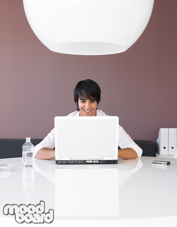 Man Using Laptop at White Table