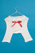 underwear hanging on a clothes hanger with a red bow tie